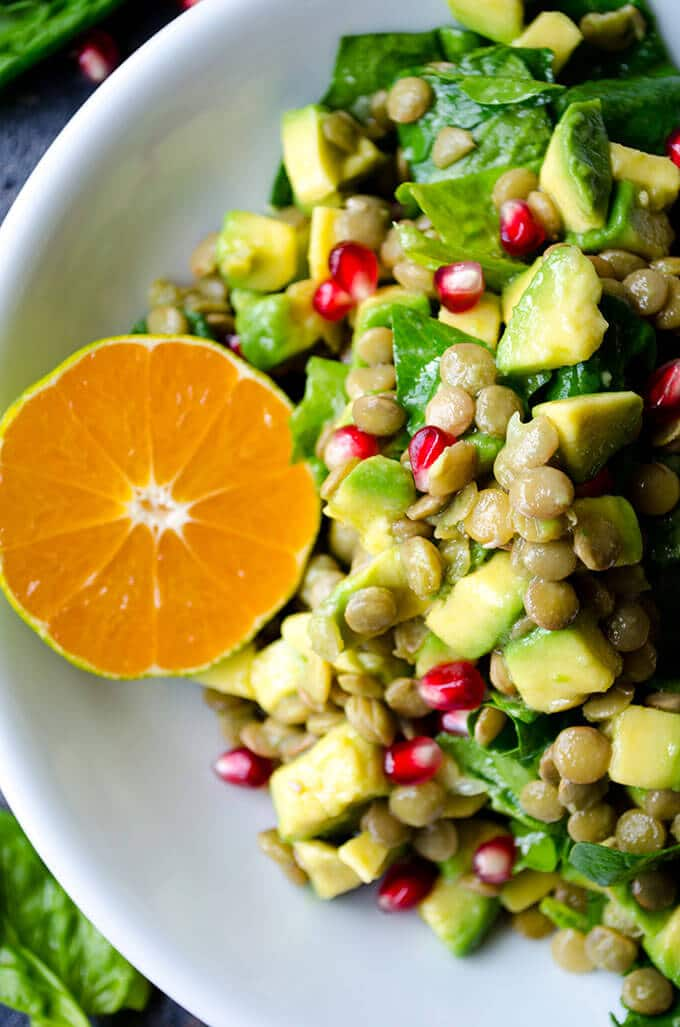 Vegan Lentil Salad with spinach, mandarin, avocado and pomegranate in a white bowl