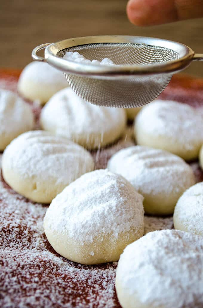 A hand sifting powdered sugar over melting moment cookies.