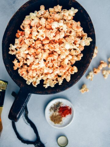 Spicy popcorn served in a large wooden bowl accompanied by spices in a small plate.