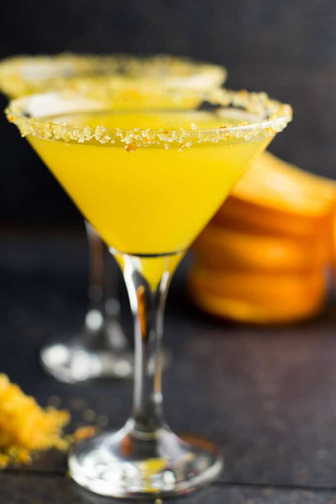 Orange martini in martini glasses that are rimmed with zesty orange sugar.