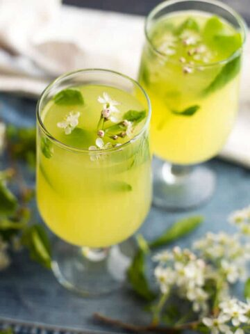 Ginger lemonade garnished with blossoms in two glasses