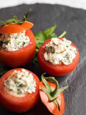 Cheese Stuffed Tomatoes served on a black stone