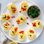 Deviled eggs without mayo garnished with parsley and red bell pepper on a white plate.