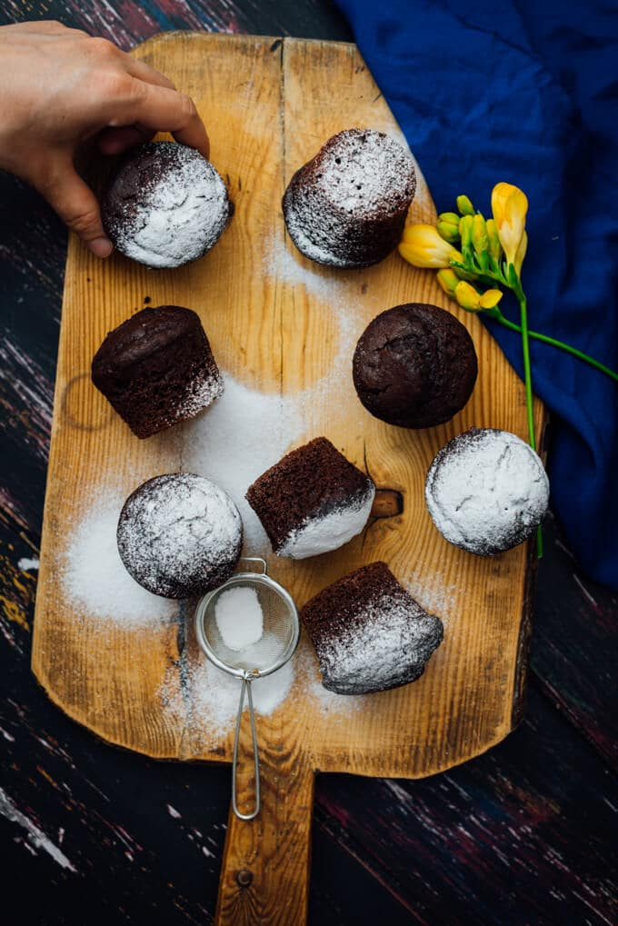 Grabbing one of the Buttermilk Chocolate Muffins dusted with powdered sugar on a wooden board