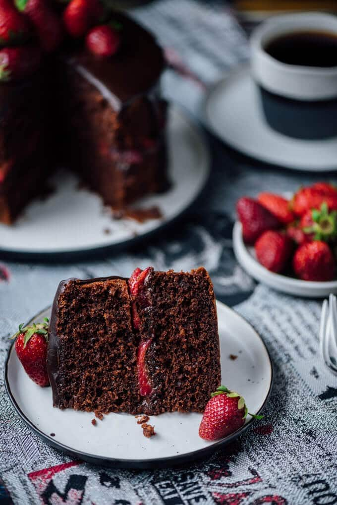 A slice of chocolate cake with strawberry served on a plate. Strawberries and coffee accompany.