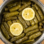 Dolmades with lemon slices on the top in a pot.