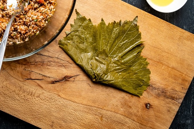 A grape leaf is stuffed with rice and folded on a wooden board.