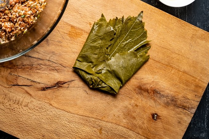 How to stuff grape leaves is shown on a wooden board.
