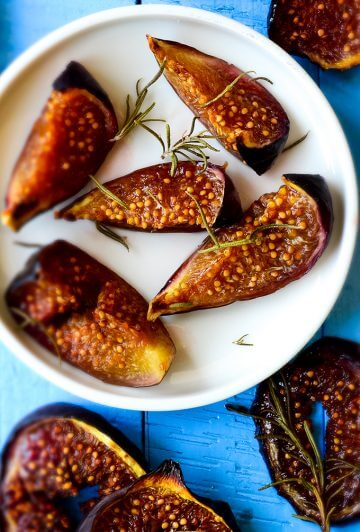 Roasted figs with rosemary and honey on white plate