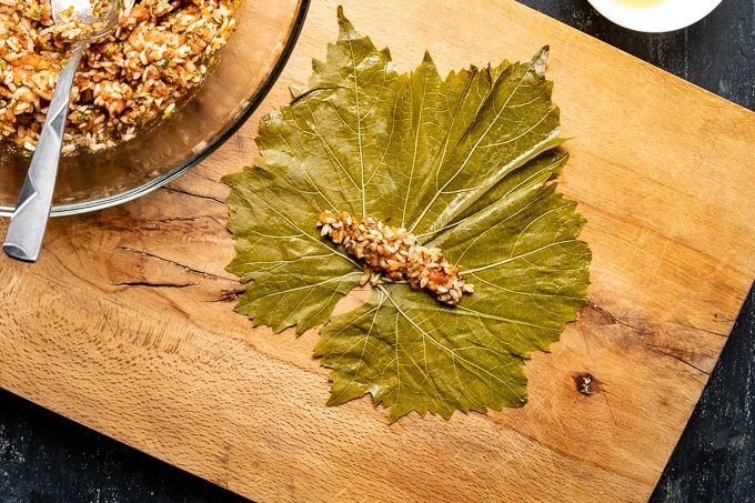 Some rice filling mixture is put on a vine leaf on a wooden board, filling bowl on the side.