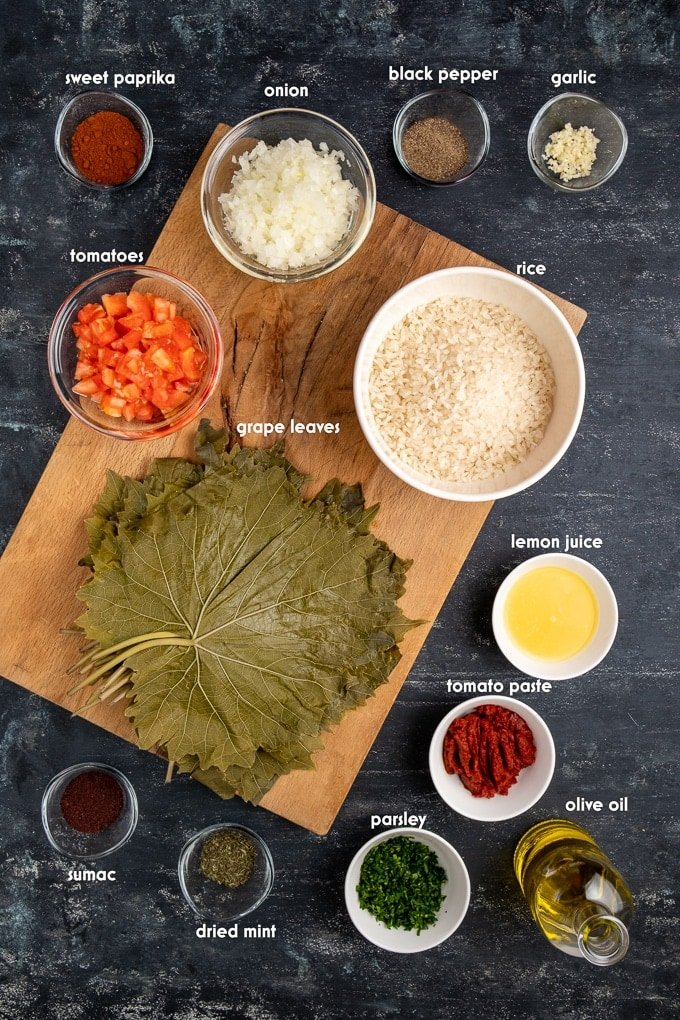 Ingredients for stuffed grape leaves on a dark background.