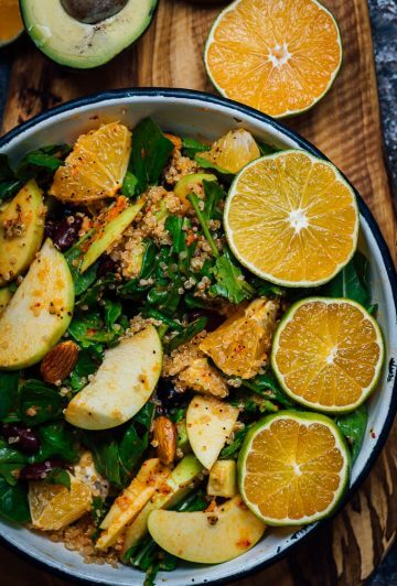 Vegan Quinoa Salad with apples and oranges in a bowl on a wooden board