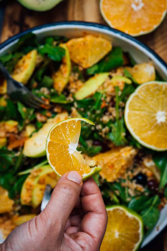 A hand holding a slice of orange over a vegan quinoa salad