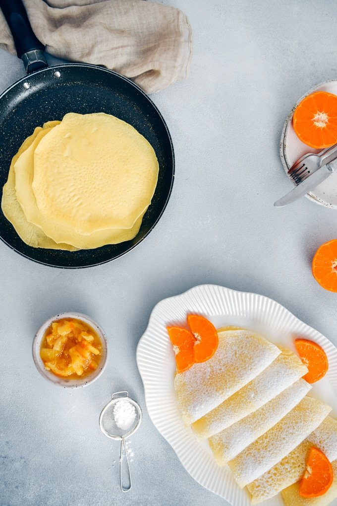 Rice flour crepes garnished with orange slices and powdered sugar.