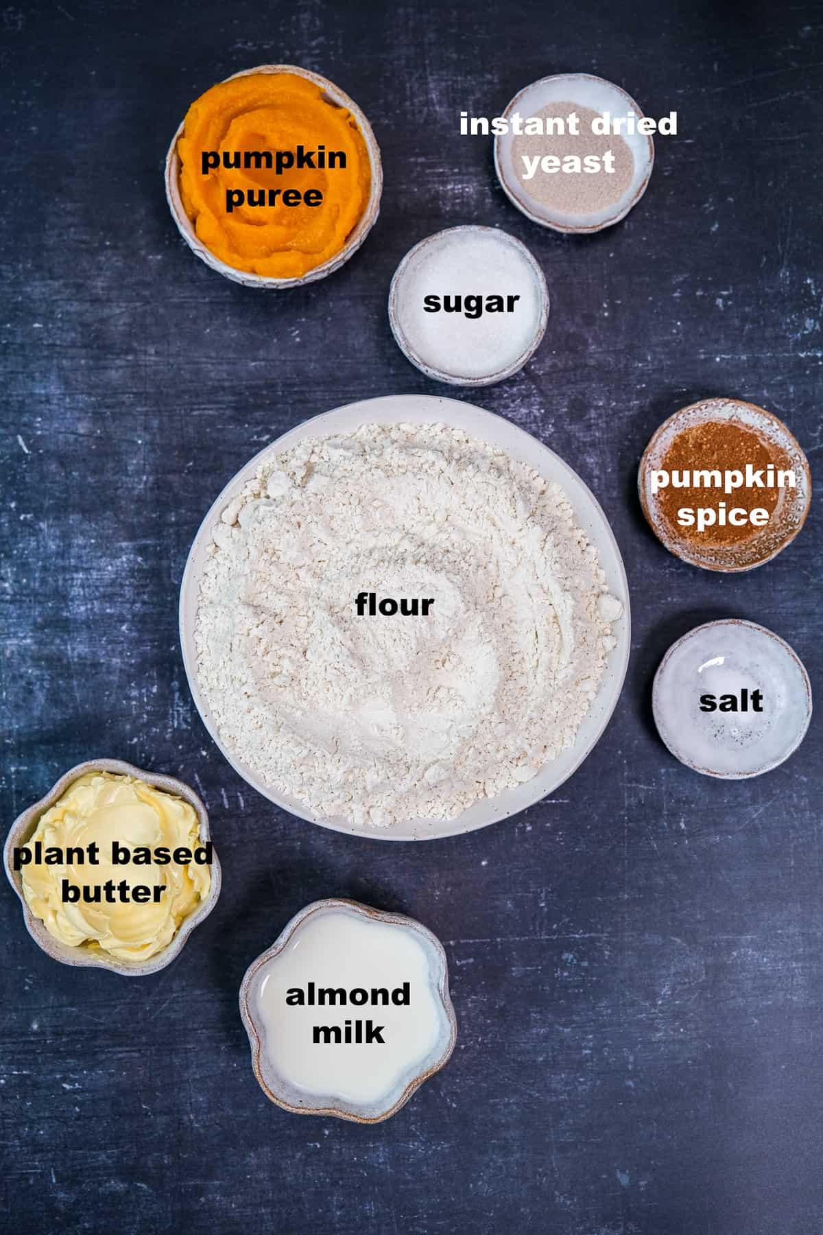 Flour, pumpkin puree, vegan butter, pumpkin pie spice, almond milk, sugar and instant yeast all in separate bowls on a dark background.