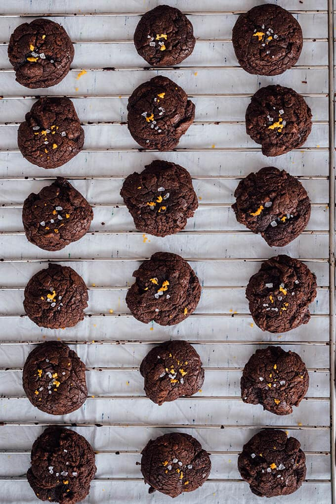 Chocolate Citrus Cookies with melted chocolate and mandarin zest cooling on a wire rack.