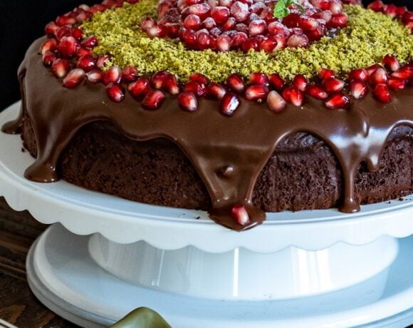 Christmas chocolate cake with ganache, pomegranate seeds and ground pistachio on a cake stand.