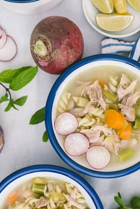 Chicken noodle soup with winter vegetables in white bowls