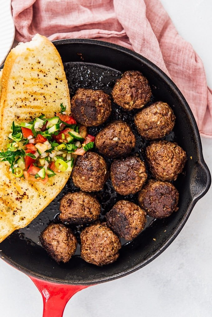 Turkish kofta and a slice of toasted bread topped with salad in a cast iron pan.