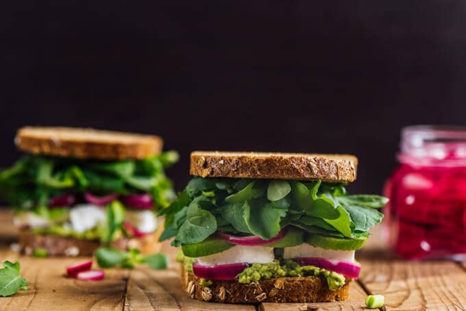 Healthy breakfast sandwich with cheese, avocado, cucumber, herbs and onion pickles