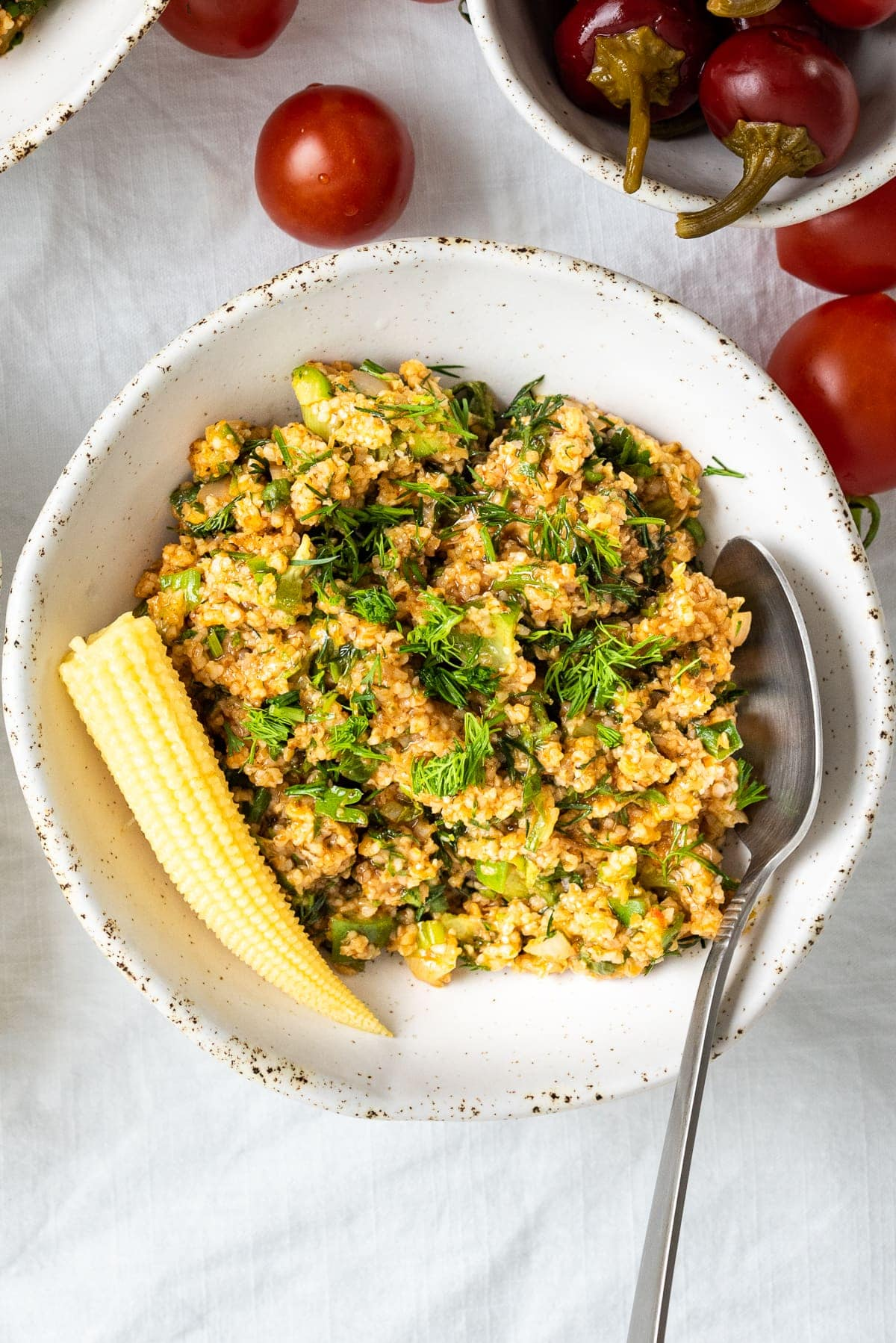 Turkish bulgur salad kısır in a white ceramic bowl, a spoon inside it and a pickled baby corn on the left top.