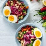 White bean salad garnished with pickled onions and hard boiled eggs in two bowls.