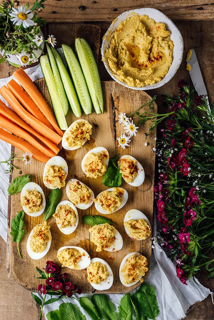 Healthy Deviled Eggs with hummus are on a snack board accompanied by cucumber and carrot sticks.