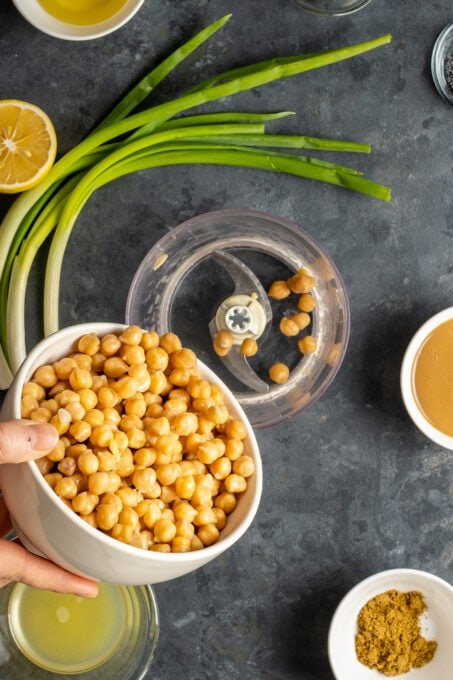 A hand putting cooked chickpeas from a white bowl into a food processor. Green onions, lemon, tahini and spices are on the side.