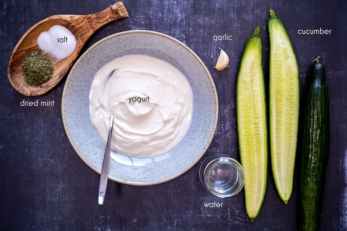 Yogurt in a large bowl, halved cucumber, a whole cucumber, garlic, water in a small bottle, salt and dried mint in a wooden bowl on a dark background.