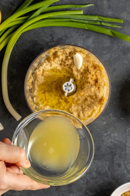 A hand pouring lemon juice from a small glass bowl over mashed chickpeas in a food processor.