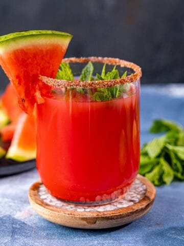 Watermelon margarita in a small glass garnished with a small slice of watermelon and mint leaves.