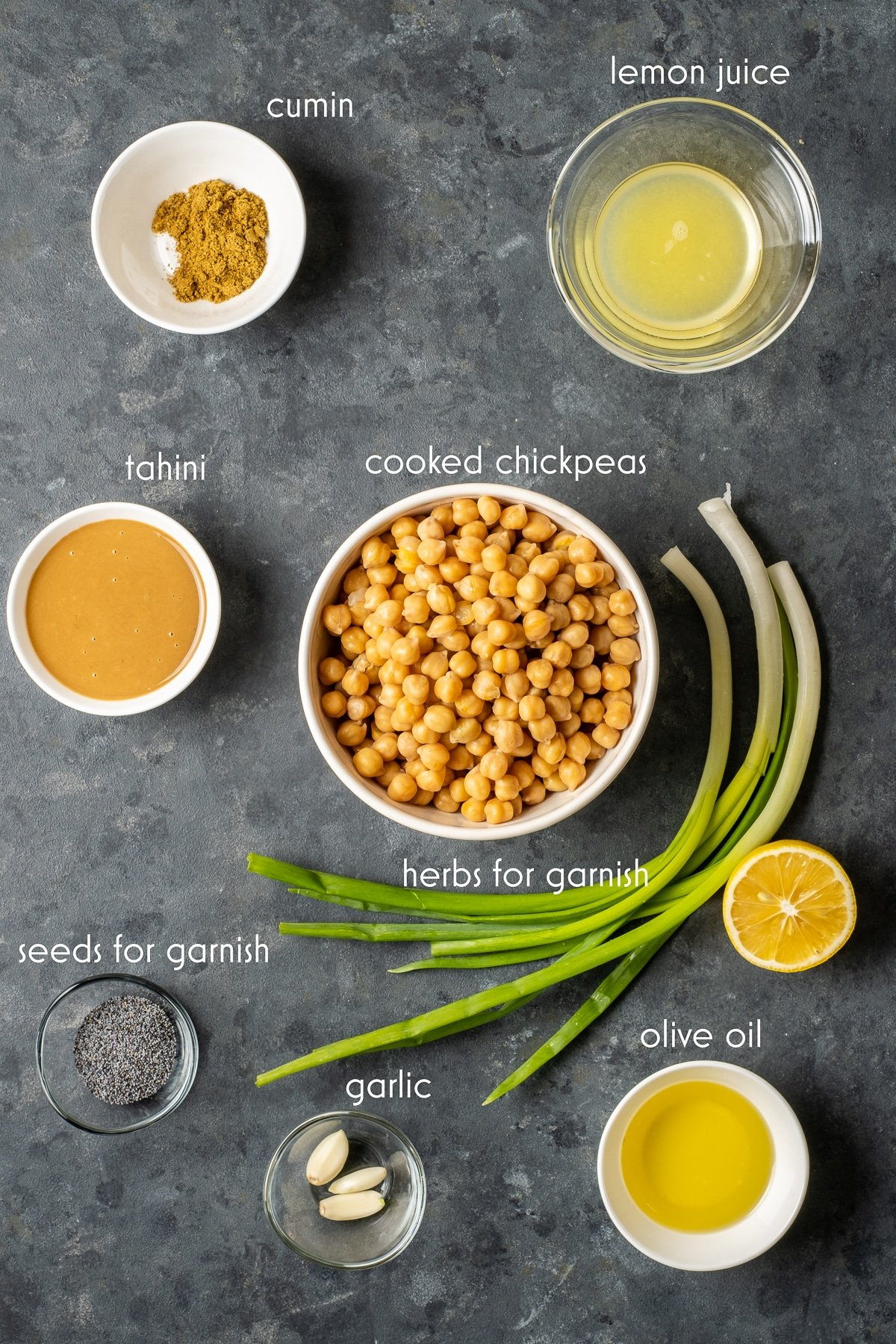 Cooked chickpeas, lemon juice, olive oil, salt and cumin, tahini, garlic cloves in separate bowls and green onions on the ground from top view.