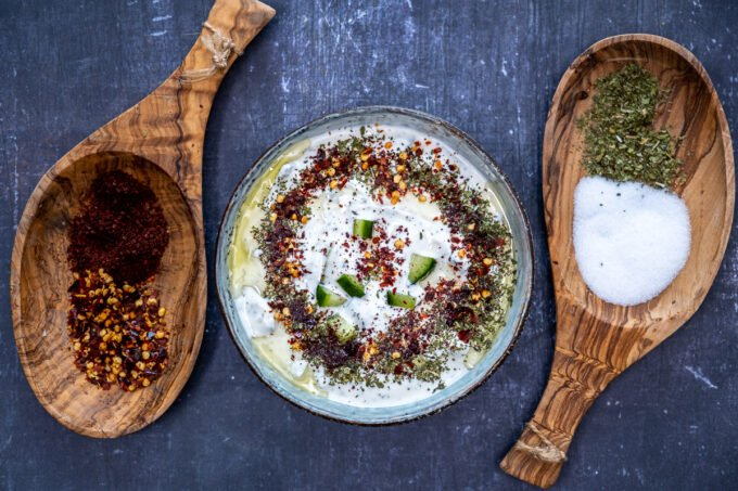Turkish cacik topped with olive oil, dried mint, sumac and red pepper flakes in a bowl and two wooden bowls with spices on both sides of the bowl on a dark background.