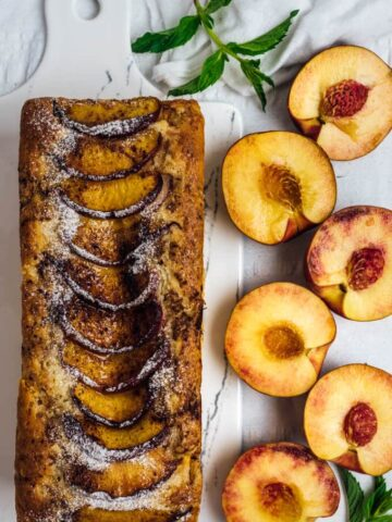 Peach Bread with Walnuts is wonderfully moist and flavorful thanks to fresh peach chunks and cinnamon on its top.