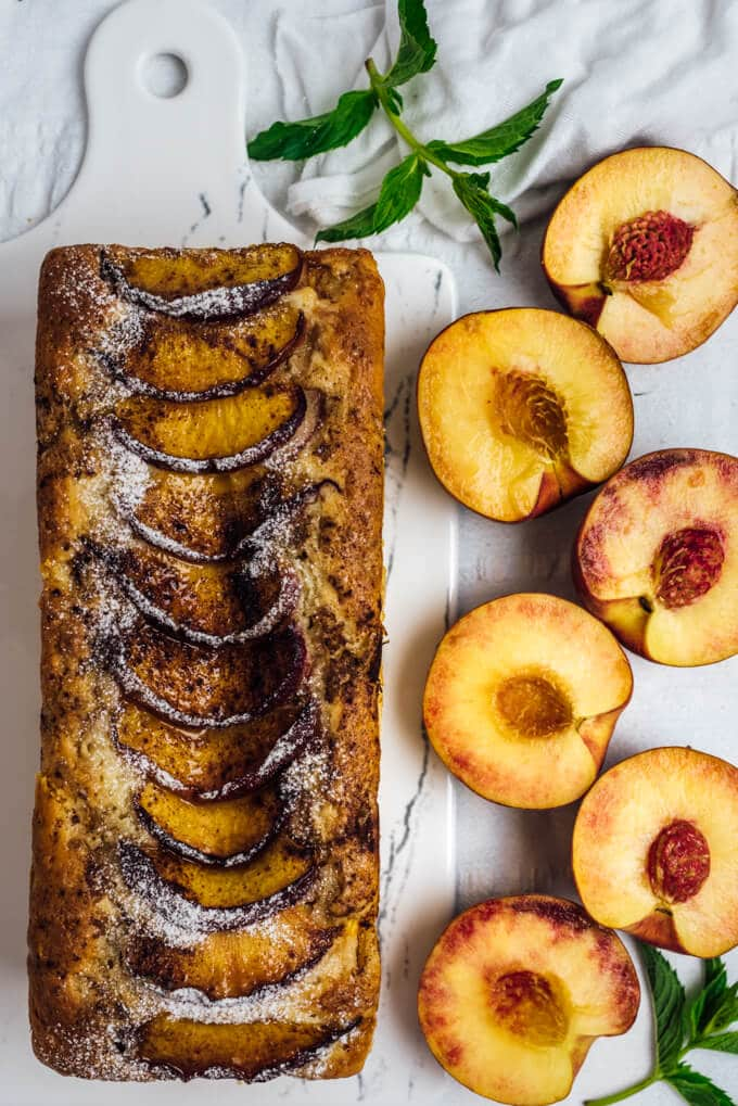 Fresh peach bread with peach slices on a white cutting board