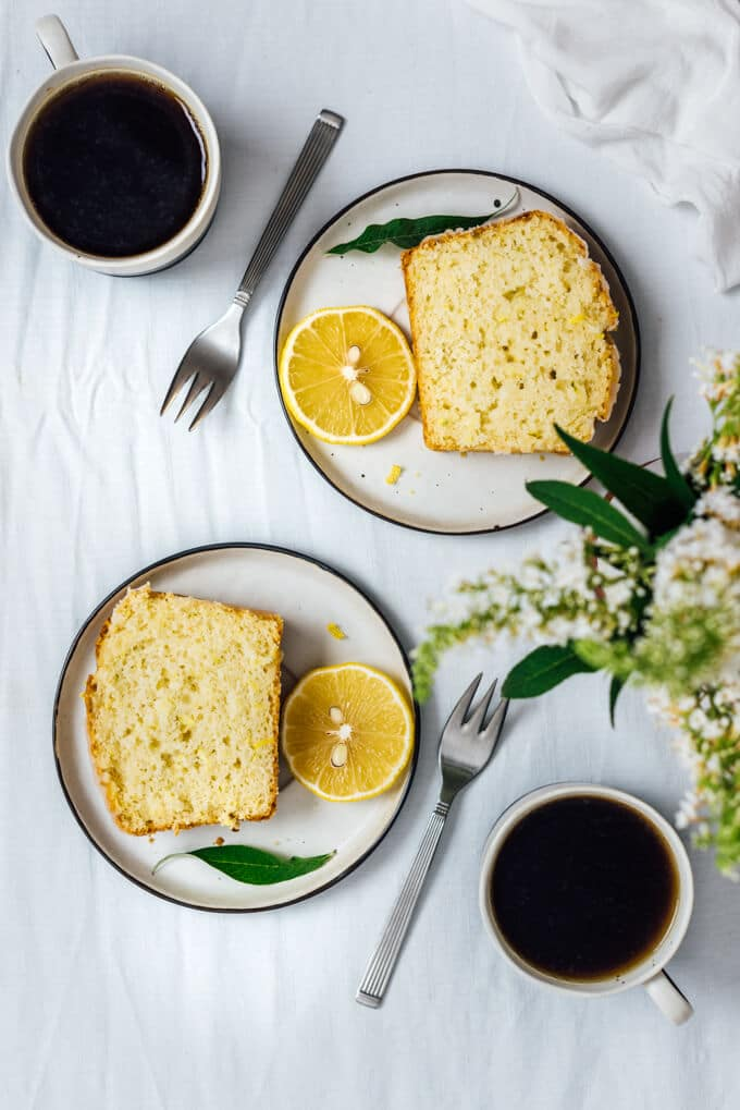 Lemon zucchini cake slices on two plates accompanied by two cups of coffee.