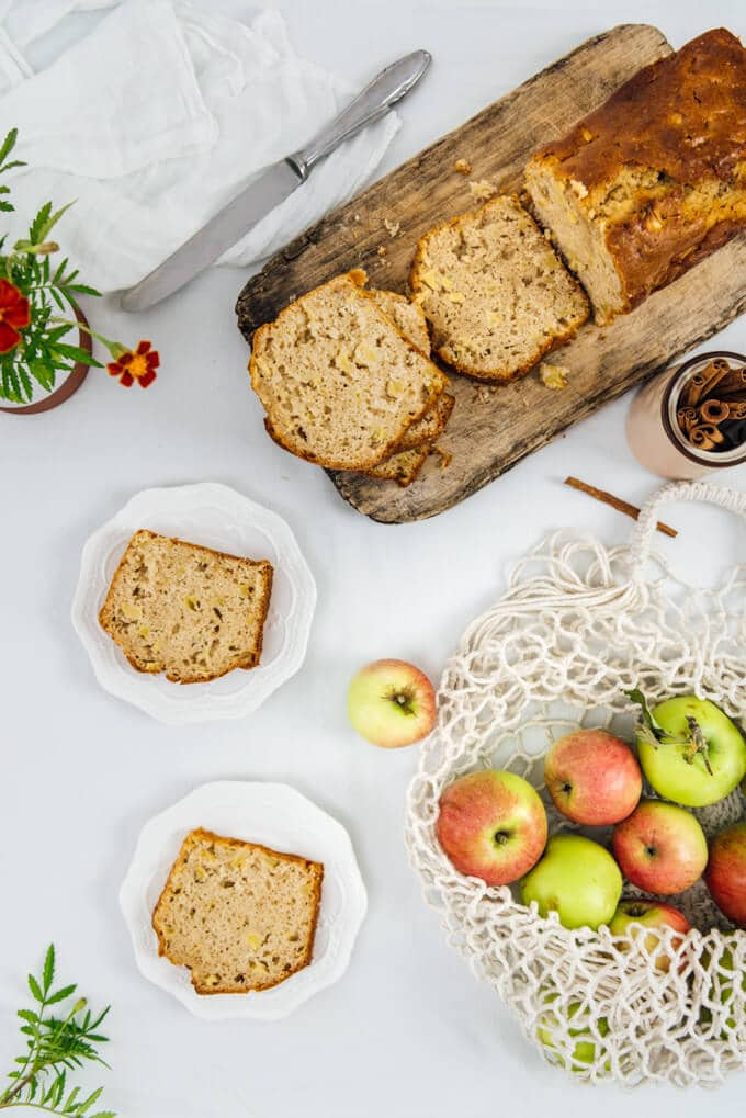 Chunky Apple Cinnamon Bread  sliced on a wooden board and served on two white plates, apples in a string bag.
