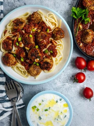 Tomato Chili Sauce Meatballs served on pasta in a white bowl.