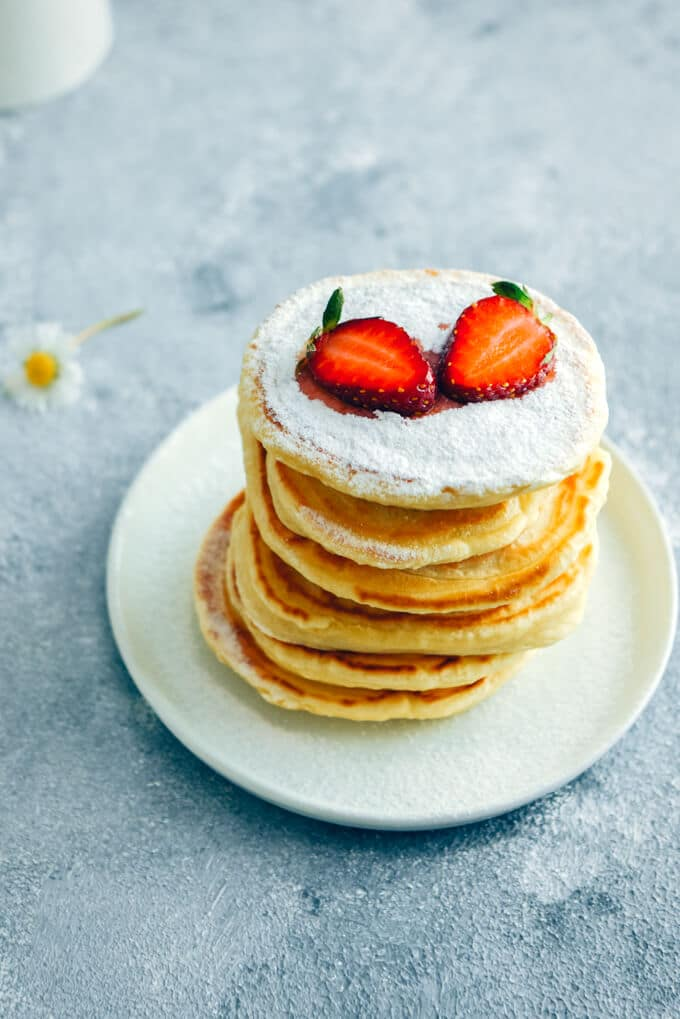 Almond milk pancakes with powdered sugar and strawberries on a grey background.