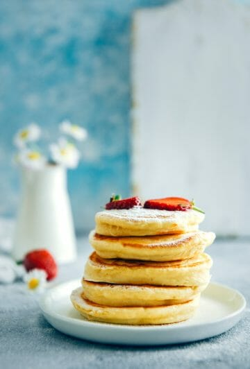 Almond milk pancakes with powdered sugar and strawberries. Spring flowers on the back.