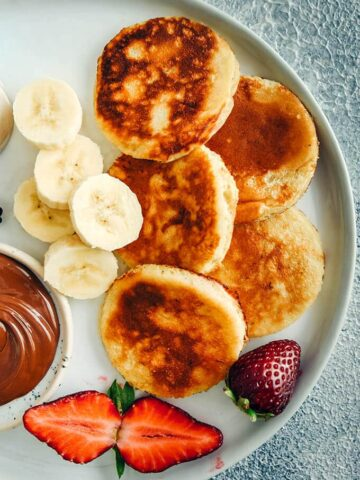 Banana yogurt pancakes with banana slices, strawberries and chocolate on a white plate