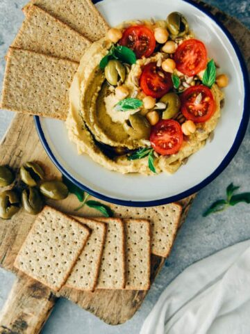 Hummus without tahini garnished with olives, tomatoes, herbs and sun flower seeds served with crackers.