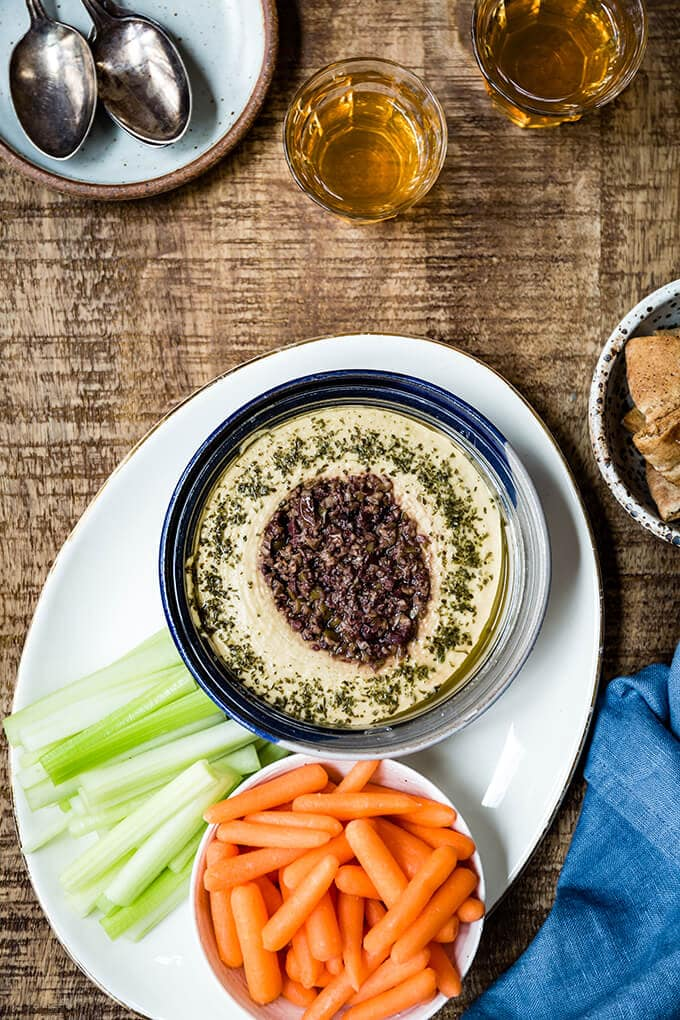 Hummus in a blue bowl served with raw veggies on the side