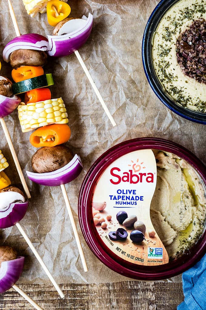 Vegetarian kabobs and hummus bowls on baking paper