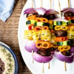 Colorful veggie kabobs on a white plate accompanied by a blue napkin and hummus on the side.