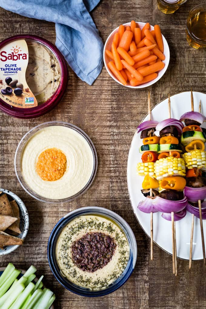 Vegetable shish kabob accompanied by hummus bowls and carrots on the side