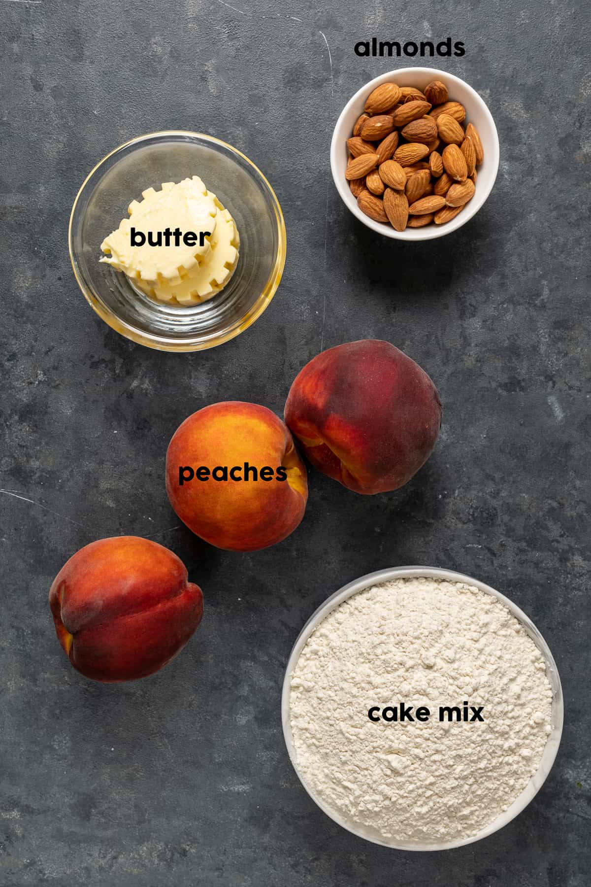 Peaches, butter, almonds and a bowl of cake mix on a dark background.