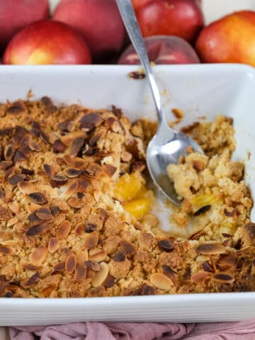 Peach cobbler with cake mix topped with almonds in a white baking pan with a spoon in it and fresh peaches behind it.
