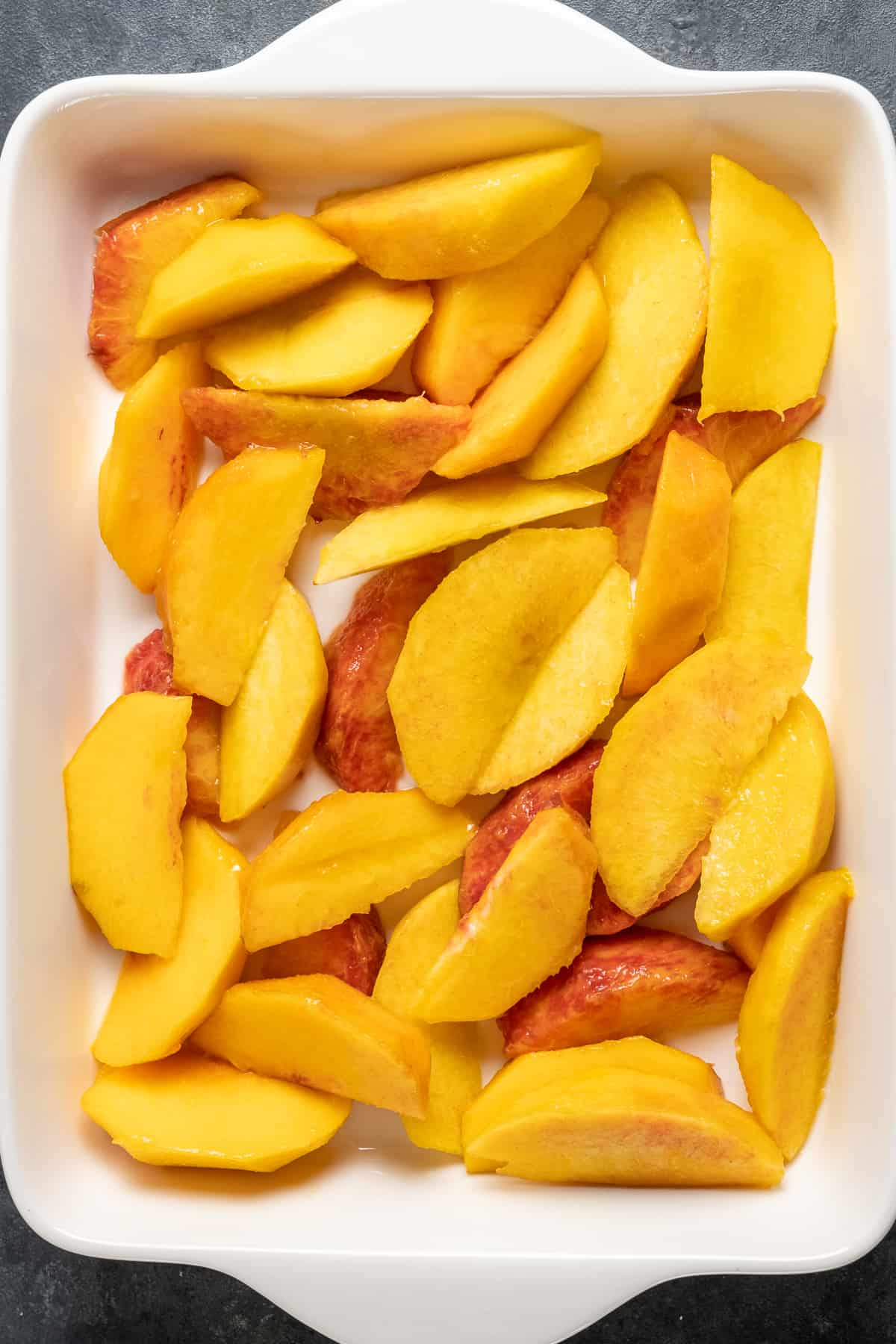 Peach slices covering the bottom of a white rectangular baking pan.