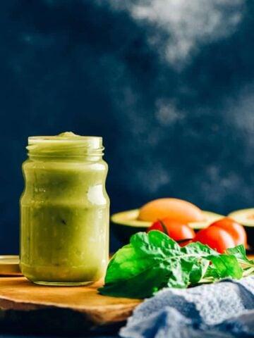 Avocado dressing in a glass jar on a wooden board